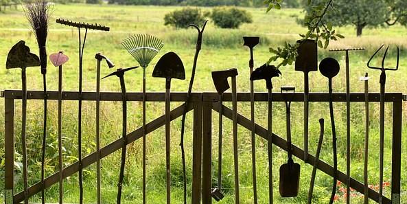 tuingereedschappen vastgemaakt aan hek
